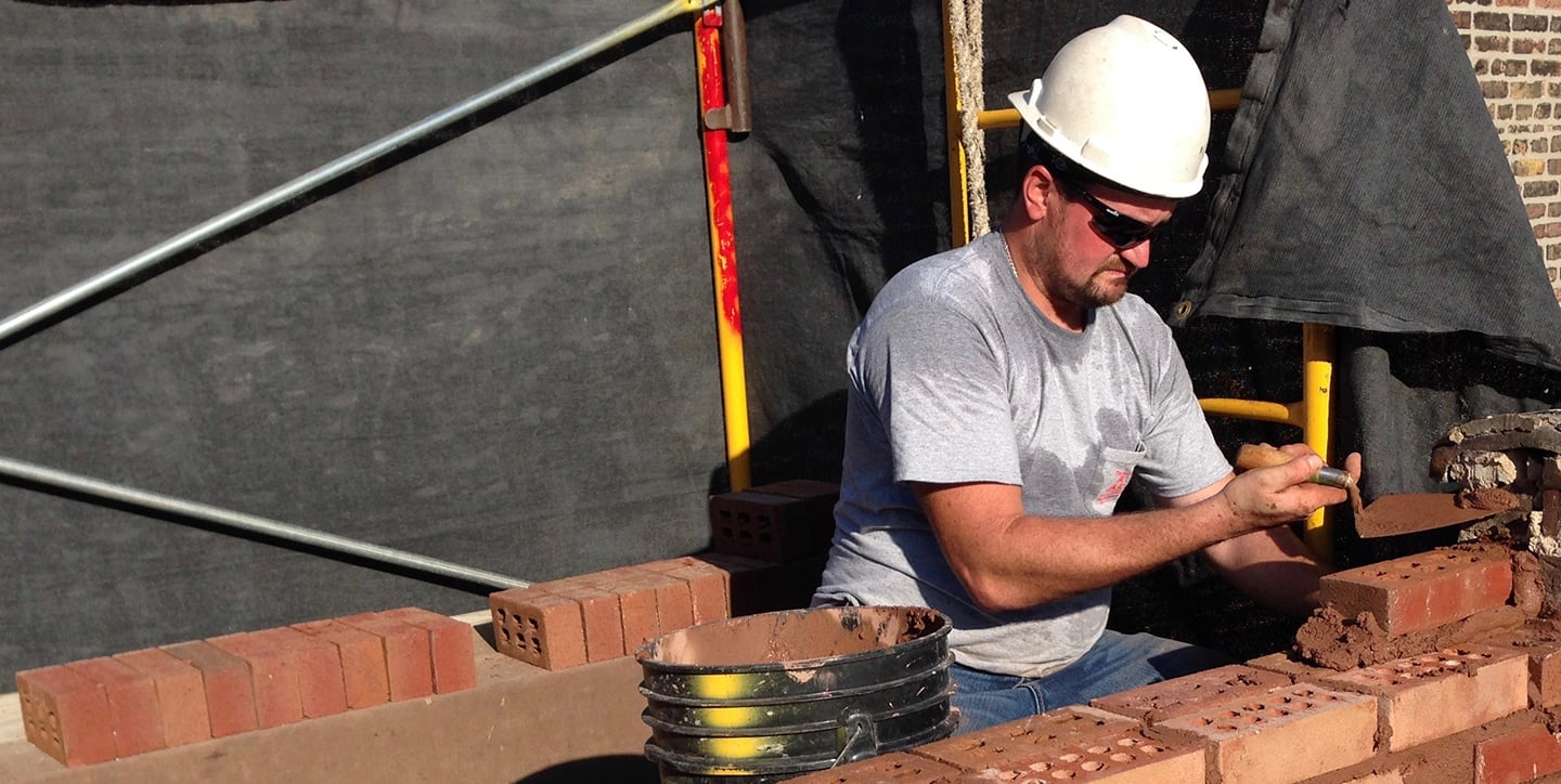 A licensed mason laying brick