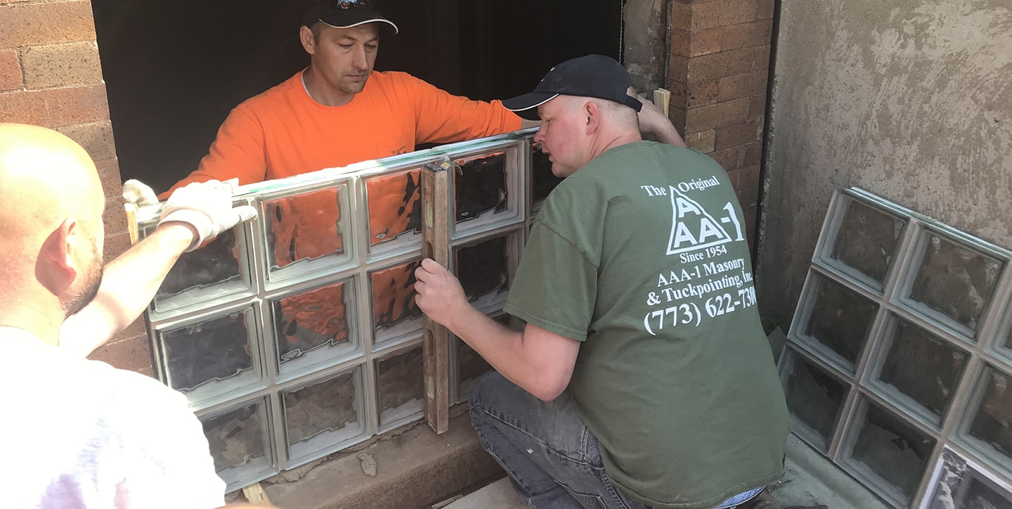 AAA-1 licensed masons installing a glass block window in a basement opening