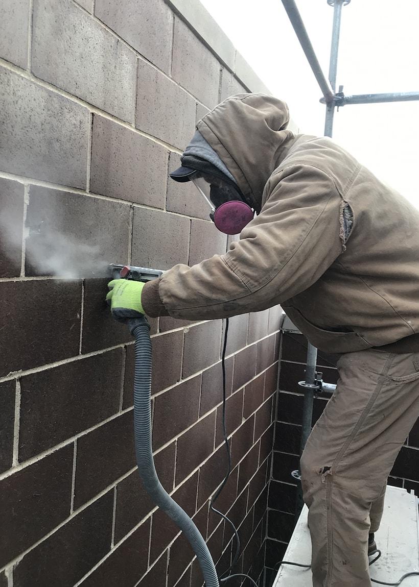 AAA-1 licensed mason Bronek grinding a cinder block wall