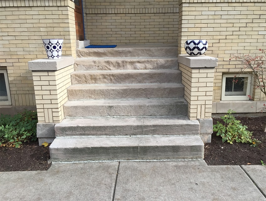 Limestone entryway steps with stoop walls rebuilt using original 95-year-old capstones and footers