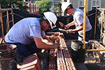 AAA-1 masons rebuilding a parapet wall comprised of three wythes of brick.