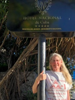 AAA-1 client Ann Halverson wearing her AAA-1 Masonry t-shirt while standing next to the Hotel Nacional de Cuba sign in Havana.