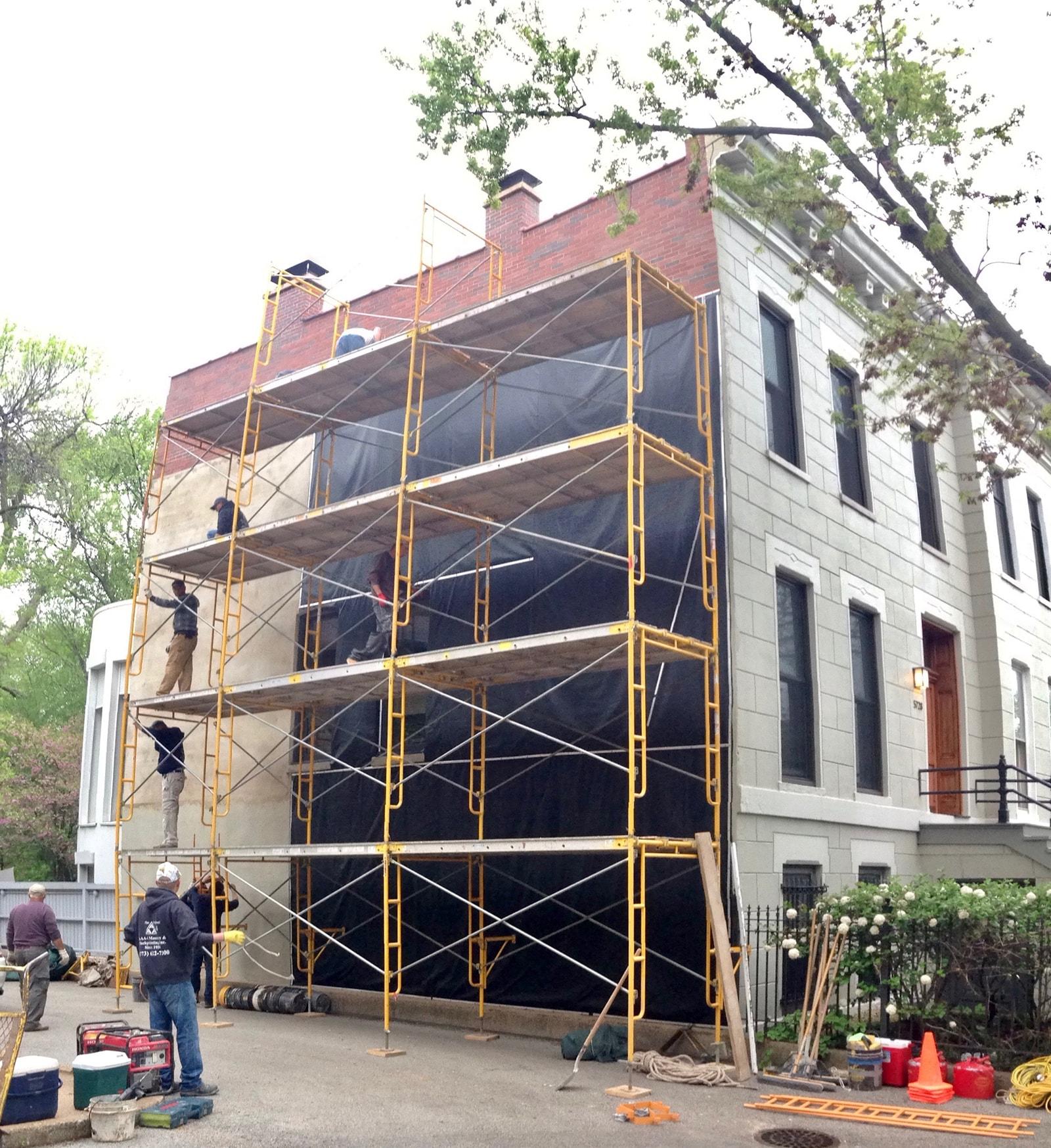 Workers installing vinyl tarpaulins on wall of masonry building