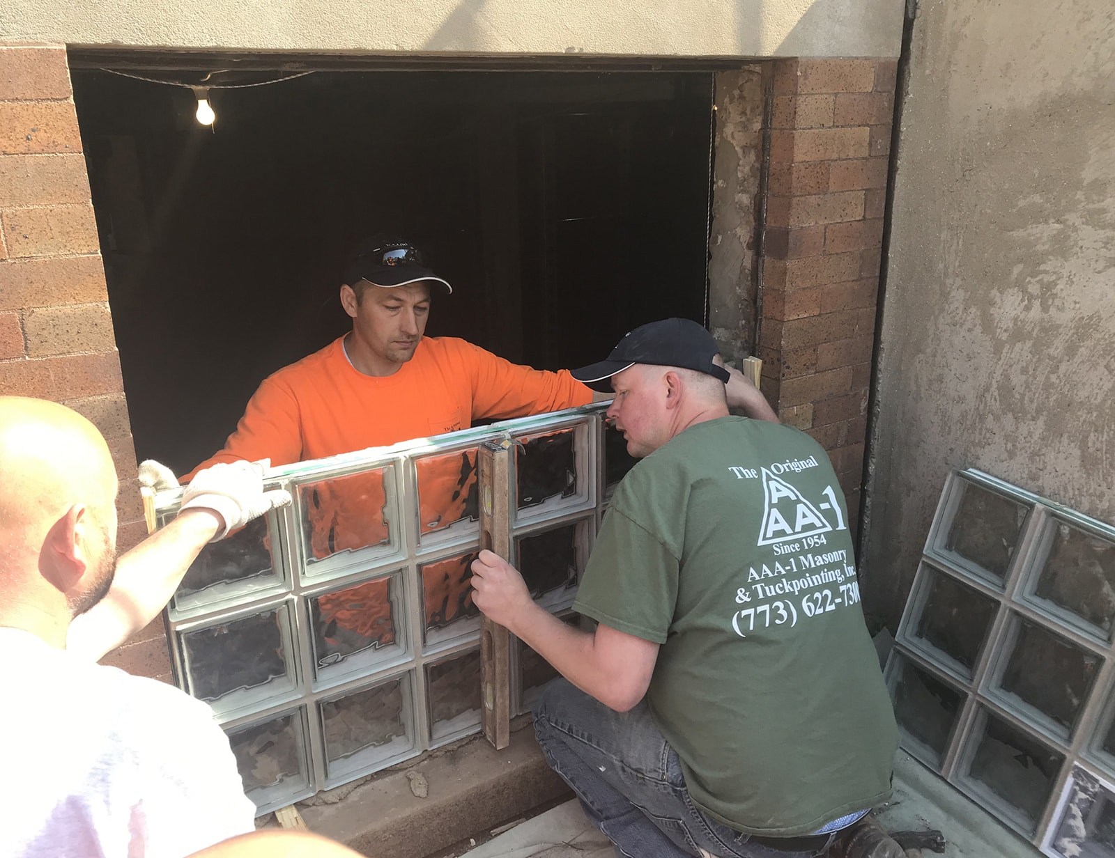 AAA-1 licensed masons installing a wavy-styled glass block window unit in a basement opening