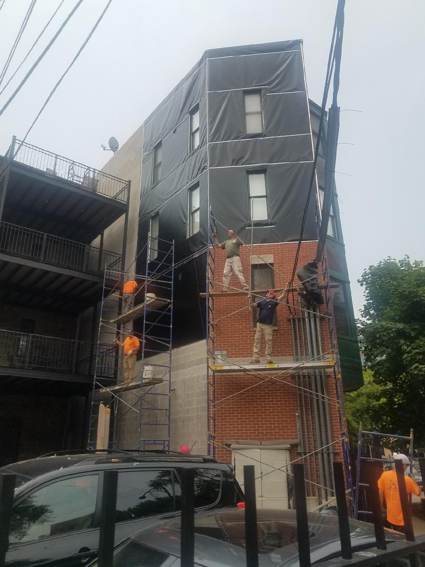 Workers installing heavy-duty vinyl tarpaulins on a building in Lincoln Park, Chicago