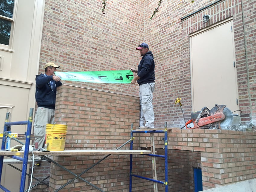 Two masons placing drip edges and flashing on new wall of staircase up.