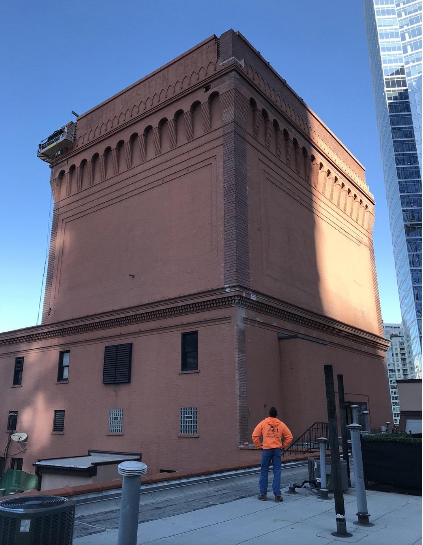 Foreman Mirek looks up at a brick elevator penthouse