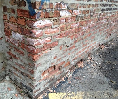 A neglected 105-year-old exterior brick foundation wall