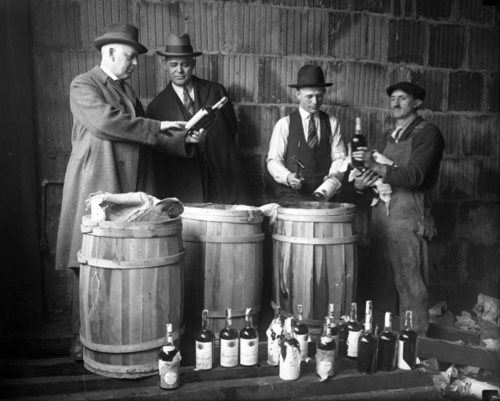 A Prohibition liquor bust in front of a telephone block masonry wall