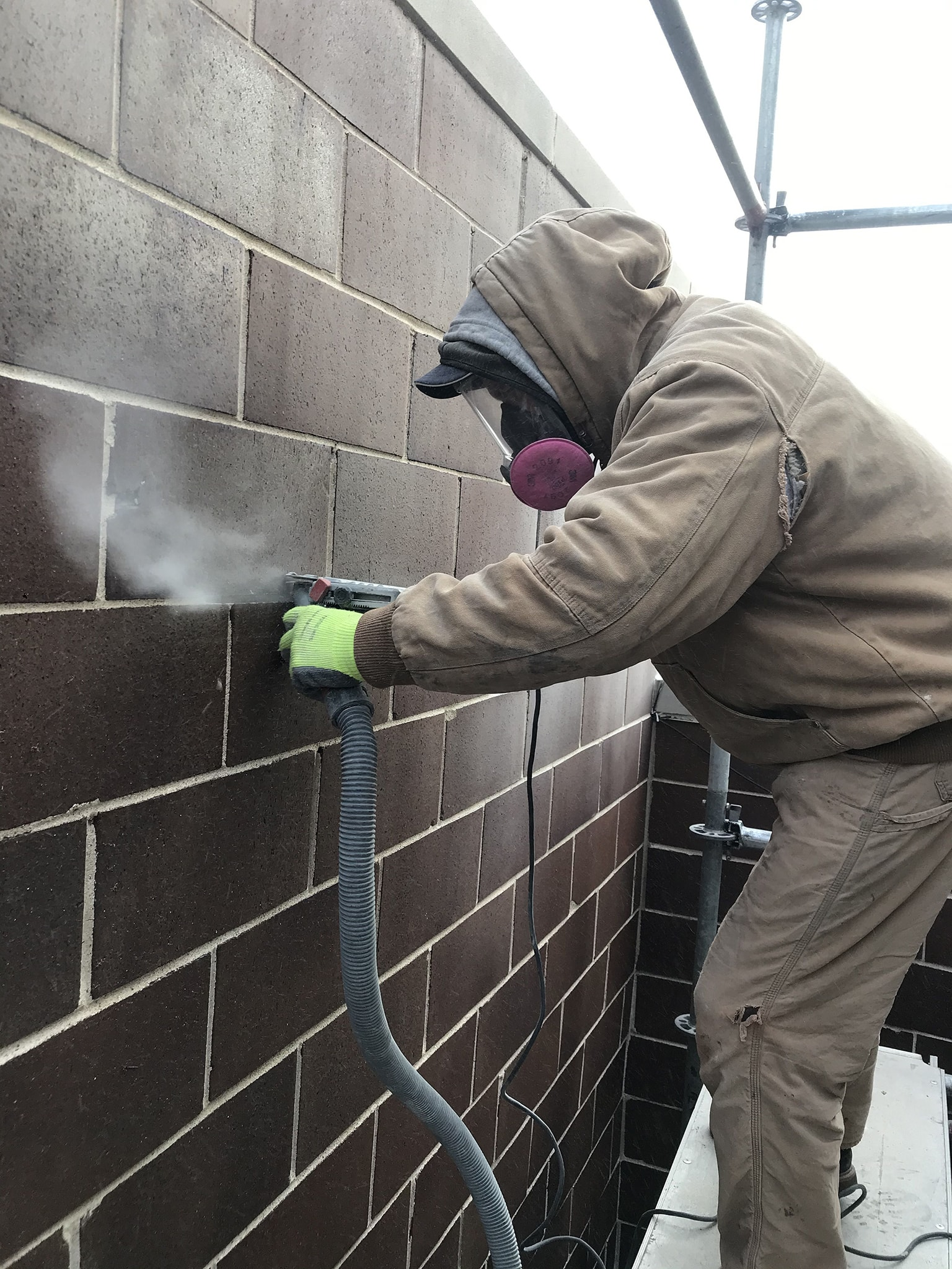 A licensed mason grinding a mortar joint