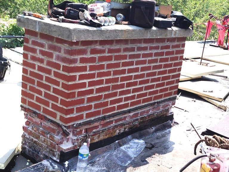 A concrete chimney cap cracked in multiple places and very poor mortar adhesion between the bricks, with extensive brick erosion and failed mortar at the base of the chimney.