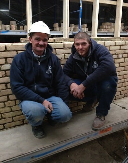 Peter and Mark stand in front of their freshly-constructed foundation wall despite the freezing temperatures outside. Ambient temperature inside the protected work site remains constant at 50 F.
